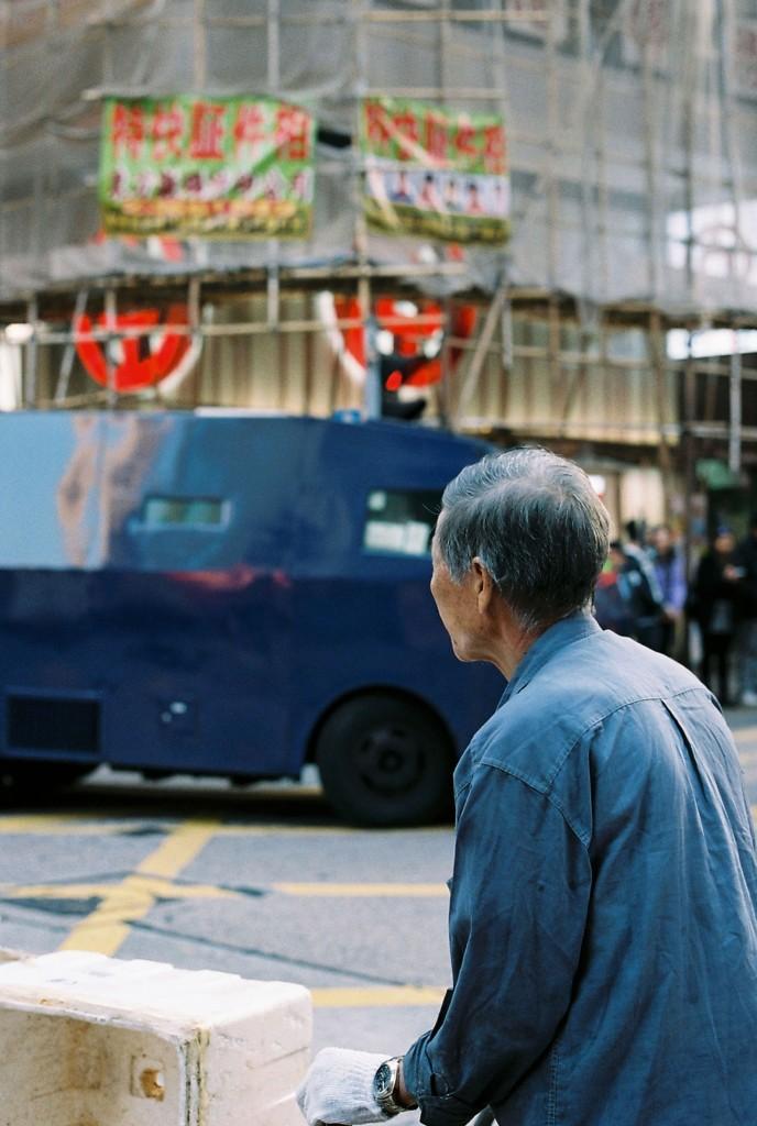 Arbeitender älterer Mann auf der Straße in Kowloon, ein gängiger Anblick in Hong Kong