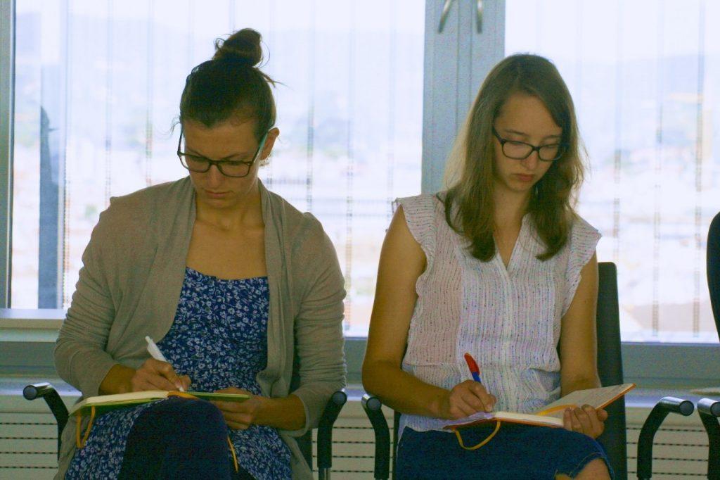 Zwei Teilnehmerinnen der Akademie für Neu- und Junglehrpersonen machen sich Notizen, um sich auf die abschließende Reflexionsphase vorzubereiten.