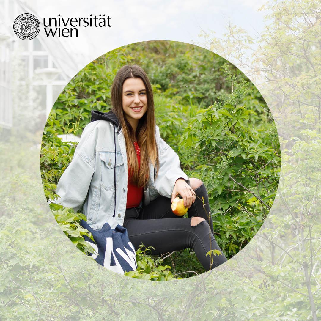 Anna Lena sitzt im Grünen vor einem Unigebäude.