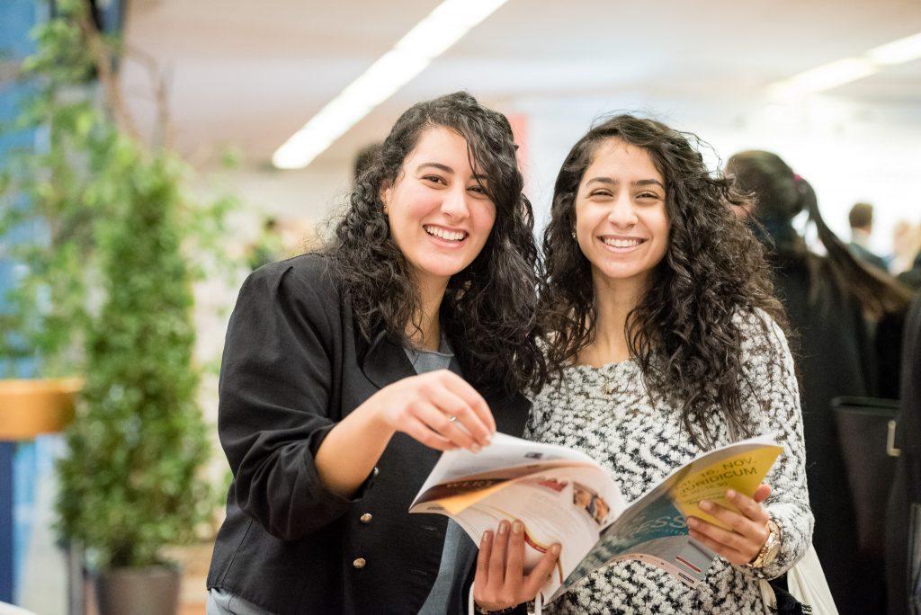 Zwei Studierende lächeln und blättern in einem Magazin