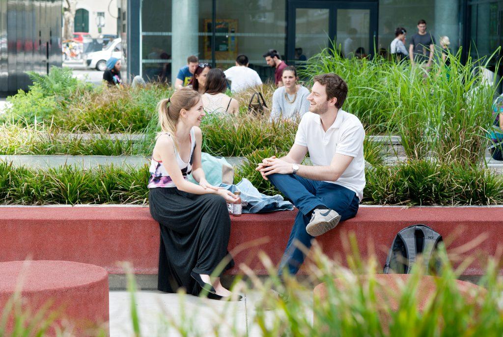 Zwei Studierende unterhalten sich im Freien